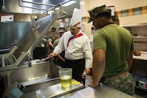 Stephen Dziedzic, executive chef, Sodexo, instructs Marines in cold food preparation at Mess Hall 128, Camp Lejeune, N.C., July 11, 2018. The training teaches methods to Marine food service specialists to improve the basic services involving baking, roasting, recipe use, cold food preparation and grilling. (U.S. Marine Corps photo by Lance Cpl. Ashley Gomez)