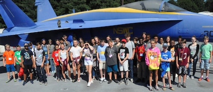 IMAGE: KING GEORGE. Va. (June 29, 2018) - Middle school students stand in front of an F-18 used as a ground plane for testing and evaluating the hazards of electromagnetic radiation to ordnance at the Naval Surface Warfare Center Dahlgren Division (NSWCDD) Electromagnetic Environmental Effects test site. The students toured NSWCDD in conjunction with their academy activities at the 2018 STEM Summer Academy. They saw the real-world applications during their tour that also featured the electromagnetic railgun, laser lethality laboratory, Potomac River Test Range, and vehicle integration technologies.