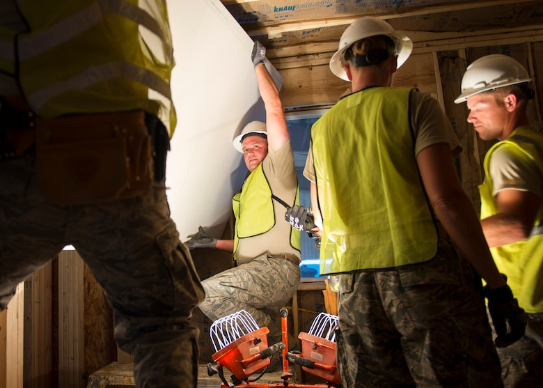 U.S. Air Force Staff Sgt. Donald Johnson, an electrician from the 133rd Civil Engineer Squadron, helps hang a sheet of drywall within a transportable modular home in Gallup, N.M., July 23, 2018.