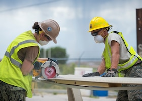 U.S. Air Force Staff Sgt. Mark Spitznogle (right), from the 133rd Civil Engineer Squadron Structures shop, holds down a piece of fascia while a U.S. Navy Seabee (left) makes a cut in Gallup, N.M., July 23, 2018.