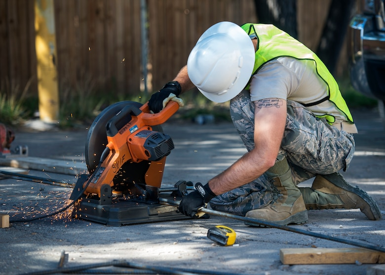 U.S. Air Force Airman 1st Class Keegan Geske, 133rd Civil Engineer Squadron Utilities shop, cuts a piece of rebar that will be used to reinforce a concrete footing on a handicap ramp for the St. Francis Catholic School in Gallup, N.M., July 24, 2018.