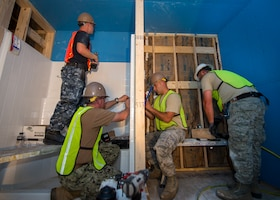 U.S. Air Force Airmen from the 133rd and 148th Civil Engineer Squadrons work alongside U.S. Navy Seabees from the Naval Mobile Construction Battalion 22 to construct transportable modular homes in Gallup, N.M., July 24, 2018.