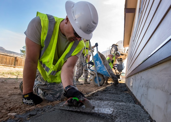 U.S. Air Force Tech. Sgt. Scott Leffler, 133rd Civil Engineer Squadron Structures shop, smooths out a recently poured apron around a recently constructed modular home in Gallup, N.M., July 25, 2018.