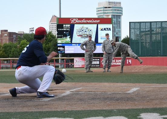 Airman 1st Class Anthony Binas throws the first pitch at a National Baseball Congress World Series baseball game.