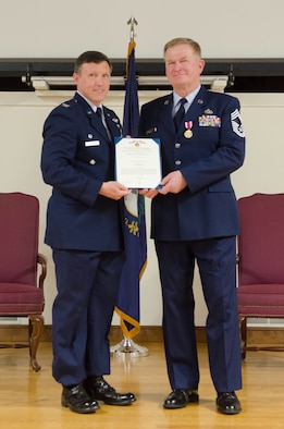 Col. Jeffrey Wilkinson (left), commander of the Kentucky Air National Guard's 123rd Airlift Wing, presents a Meritorious Service Medal to Chief Master Sgt. David Selby during Selby's retirement ceremony at the Kentucky Air National Guard Base in Louisville, Ky., May 19, 2018. Selby, the 123rd Mission Support Group superintendent, served for 39 years in the Kentucky Air National Guard. (U.S. Air National Guard photo by Master Sgt. Vicky Spesard)