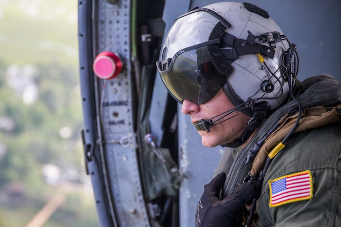 U.S. Navy AWS1 Joseph Southern flies aboard a MH-60S Knighthawk helicopter during a Search and Rescue (SAR) training exercise in Beaufort S.C., July 27, 2018.  The purpose of the exercise was to practice and hone professional skills to aid to people in immediate danger or distress. The exercise was a full community involvement including participants from the U.S. military, Naval Hospital Beaufort, and first responders within Beaufort County. (U.S. Marine Corps photo by Cpl. Erin R. Ramsay / Released)