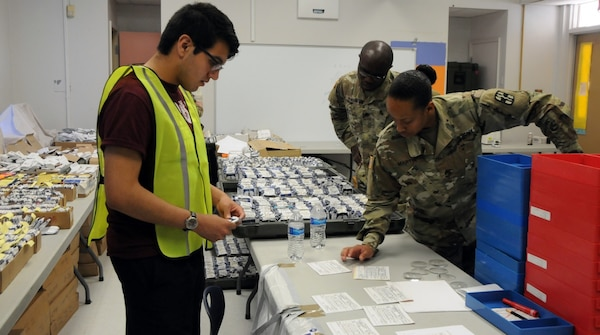 (From left) Volunteer Juan Mata, a recently graduated Socorro High School, assists Sgt. Christen Martin, an optical laboratory specialist assigned to 31st Combat Support Hospital and Spc. Kodjo Koukoua, an Army Reserve optical laboratory specialist assigned to 7252nd Medical Support Unit, in processing new eye prescriptions for eyeglass fabrication at Escontrias Early Childhood Center in Socorro, Texas. Martin and Koukoua are two of approximately 50 U.S. Army Reserve and U.S. Army Soldiers who are working in partnership with the Texas A&M Colonias program to provide medical care to El Paso County's underserved colonias population.