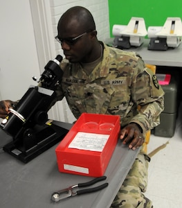 Spc. Kodjo Koukoua, an Army Reserve optical laboratory specialist assigned to 7252nd Medical Support Unit, is processing new eye prescriptions for eyeglass fabrication at Escontrias Early Childhood Center in Socorro, Texas. Koukoua is one of approximately 50 U.S. Army Reserve and U.S. Army Soldiers who are working in partnership with the Texas A&M Colonias program to provide medical care to El Paso County's underserved colonias population.