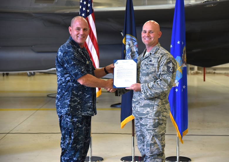 U.S. Navy Cmdr. Matthew Scott and Chief Master Sgt.(select) Matthew Coltrin, pose for a photo during the first enlisted frocking ceremony in Air Education and Training Command on Aug. 1, 2018 at Eglin AFB, Fla. A frocking ceremony allows a military member to pin on new rank prior to their promotion date. (U.S. Air Force photo by 1st Lt. Savannah Stephens)