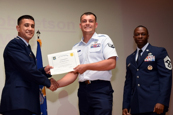 U.S. Air Force Co. Ricky Mills, 17th Training Wing commander, presents the Airman of the Quarter certificate to Senior Airman Jacob Letson, with Chief Master Sgt. Lavor Kirkpatrick, 17th TRW command chief, during the 17th TRW quarterly awards ceremony at the Base Theater on Goodfellow Air Force Base, Texas July 31, 2018. (U.S. Air Force photo by Airman 1st Class Seraiah Hines/Released)