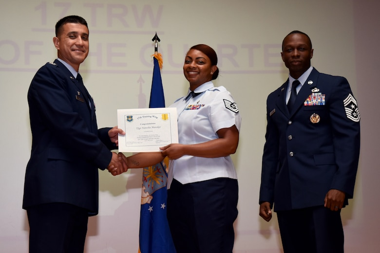 U.S. Air Force Col. Ricky Mills, 17th Training Wing commander, presents the Noncommissioned Officer of the Quarter certificate to Tech Sgt. Natosha Mansker with Chief Master Sgt. Lavor Kirkpatrick, 17th TRW command chief, during the 17th TRW quarterly awards ceremony at the Base Theater on Goodfellow Air Force Base, Texas, July 31, 2018. (U.S. Air Force photo by Airman 1st Class Seraiah Hines/Released)
