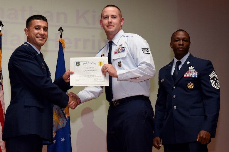 U.S. Air Force Col. Ricky Mills, 17th Training Wing commander, presents the Honor Guard Noncommissioned Officer of the Quarter certificate to Jonathan Kidd, with Chief Master Sgt. Lavor Kirkpatrick, 17th TRW command chief, during the 17th TRW quarterly awards ceremony at the Base Theater on Goodfellow Air Force Base, Texas, July 31, 2018. (U.S. Air Force photo by Airman 1st Class Seraiah Hines/Released)