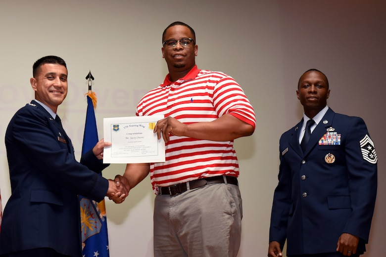 U.S. Air Force Col. Ricky Mills, 17th Training Wing commander, presents the Civilian Non-supervisory Category I of the Quarter certificate to Jacoy Owens, with Chief Master Sgt. Lavor Kirkpatrick, 17th TRW command chief, during the 17th TRW quarterly awards ceremony at the Base Theater on Goodfellow Air Force Base, Texas, July 31, 2018. (U.S. Air Force photo by Airman 1st Class Seraiah Hines/Released)