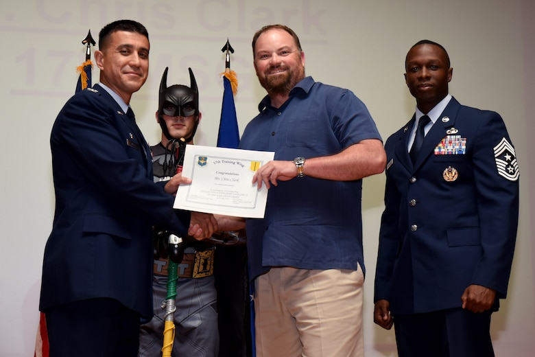 U.S. Air Force Col. Ricky Mills, 17th Training Wing commander, presents the Civilian Non-supervisory Category II of the Quarter certificate to Chris Chuck, with Chief Master Sgt. Lavor Kirkpatrick, 17th TRW command chief, during the 17th TRW quarterly awards ceremony at the Base Theater on Goodfellow Air Force Base, Texas, July 31, 2018. (U.S. Air Force photo by Airman 1st Class Seraiah Hines/Released)
