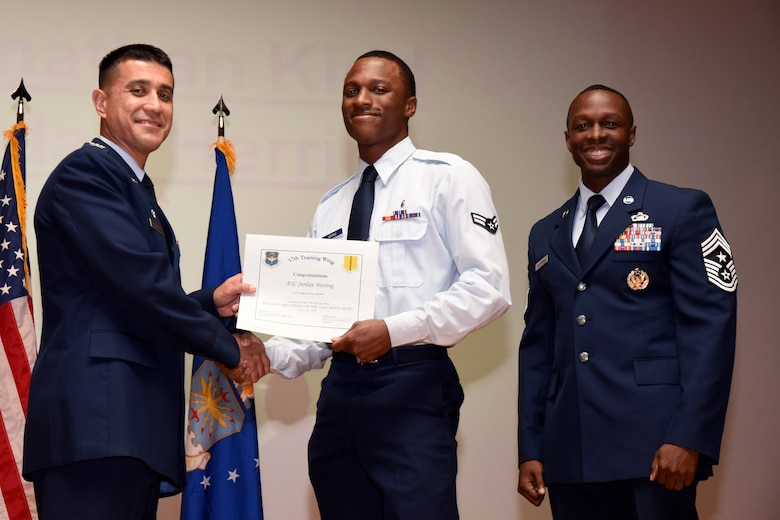 U.S. Air Force Col. Ricky Mills, 17th Training Wing commander, presents the Civilian Supervisory Category I of the Quarter certificate to Joseph Wright, with Chief Master Sgt. Lavor Kirkpatrick, 17th TRW command chief, during the 17th TRW quarterly awards ceremony at the Base Theater on Goodfellow Air Force Base, Texas, July 31, 2018. (U.S. Air Force photo by Airman 1st Class Seraiah Hines/Released)