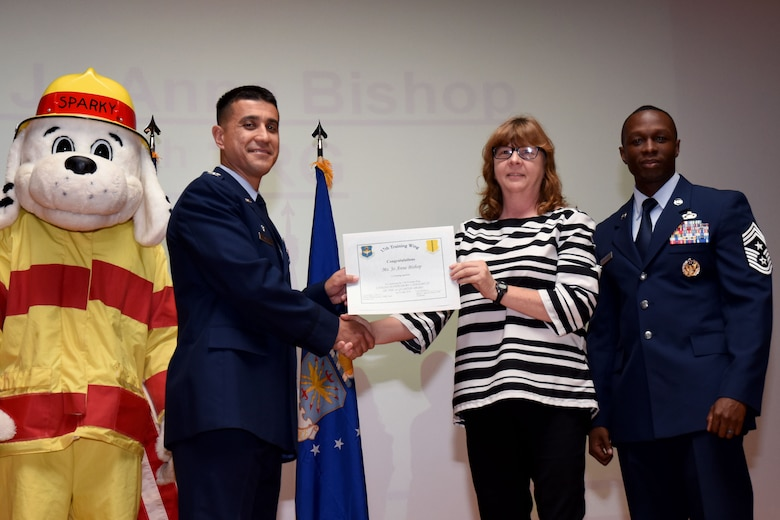 U.S. Air Force Col. Ricky Mills, 17th Training Wing commander, presents the Civilian Supervisory Category III of the Quarter certificate to Jo Anne Bishop, with Chief Master Sgt. Lavor Kirkpatrick, 17th TRW command chief, during the 17th TRW quarterly awards ceremony at the Base Theater on Goodfellow Air Force Base, Texas, July 31, 2018. (U.S. Air Force photo by Airman 1st Class Seraiah Hines/Released)