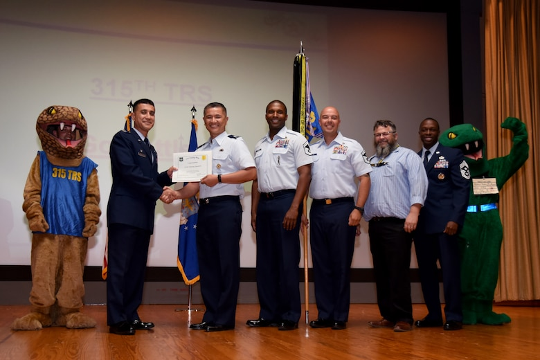 U.S. Air Force Col. Ricky Mills, 17th Training Wing commander, presents the Unit of the Quarter certificate to Lt. Col. Mark Chang, 315th Training Squadron commander, with Chief Master Sgt. Lavor Kirkpatrick, 17th TRW command chief, during the 17th TRW quarterly awards ceremony at the Base Theater on Goodfellow Air Force Base, Texas, July 31, 2018. (U.S. Air Force photo by Airman 1st Class Seraiah Hines/Released)