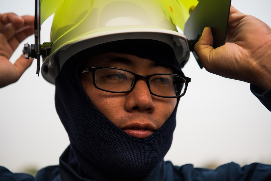 Airman 1st Class Charles Song, 9th Civil Engineer Squadron heating, ventilation and air conditioning technician, secures his personal protective equipment before working with high voltage equipment at  Beale Air Force Base, California, Aug. 2, 2018. Arch flash gear is rated to protect the wearer if there is an electric explosion. (U.S. photo by Senior Airman Justin Parsons)
