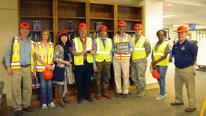 Men and women wearing safety helmets and vests standing in front of bookshelves.