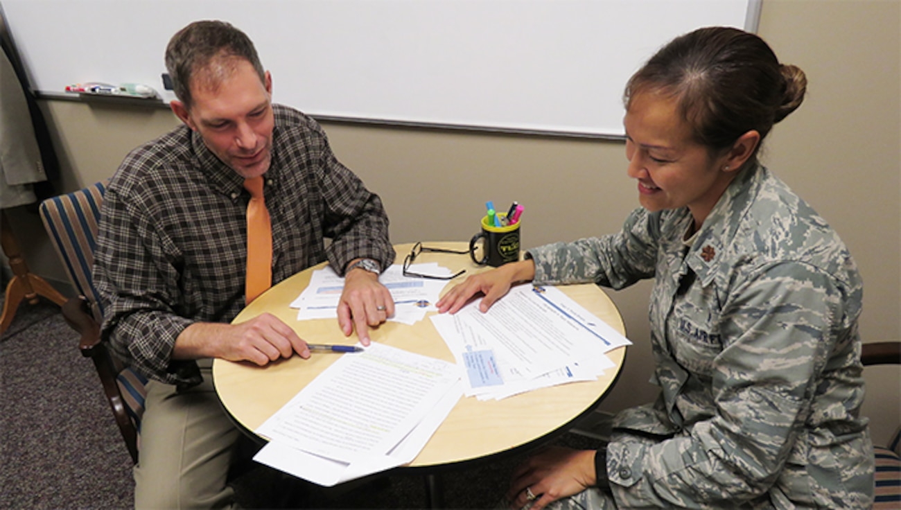 Male civilian staff member tutoring a female military officer