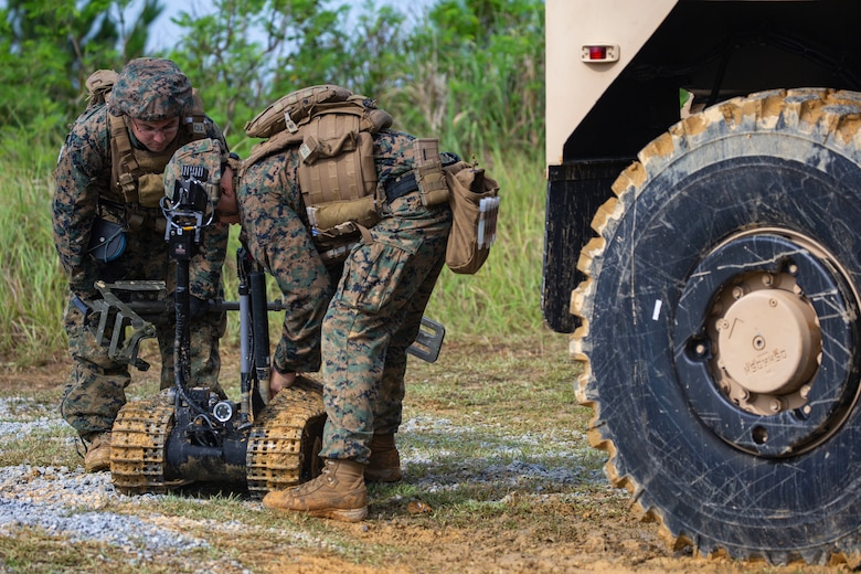 Staff Sgt. David Cain and Sgt. Maximilian Musick lift the tracks of the Mark II Talon explosive ordnance disposal robot during charge employment training Aug. 2, 2018 at Camp Hansen, Okinawa, Japan. The training taught EOD technicians to effectively neutralize IED threats with unmanned robotic platforms, safely finding and removing any hazards. Cain, a native of Fredericksburg, Virginia and Musick, a native of Phoenix, Arizona are EOD technicians with EOD Company, 9th Engineer Support Battalion, 3rd Marine Logistics Group. (U.S. Marine Corps photo by Pfc. Terry Wong)