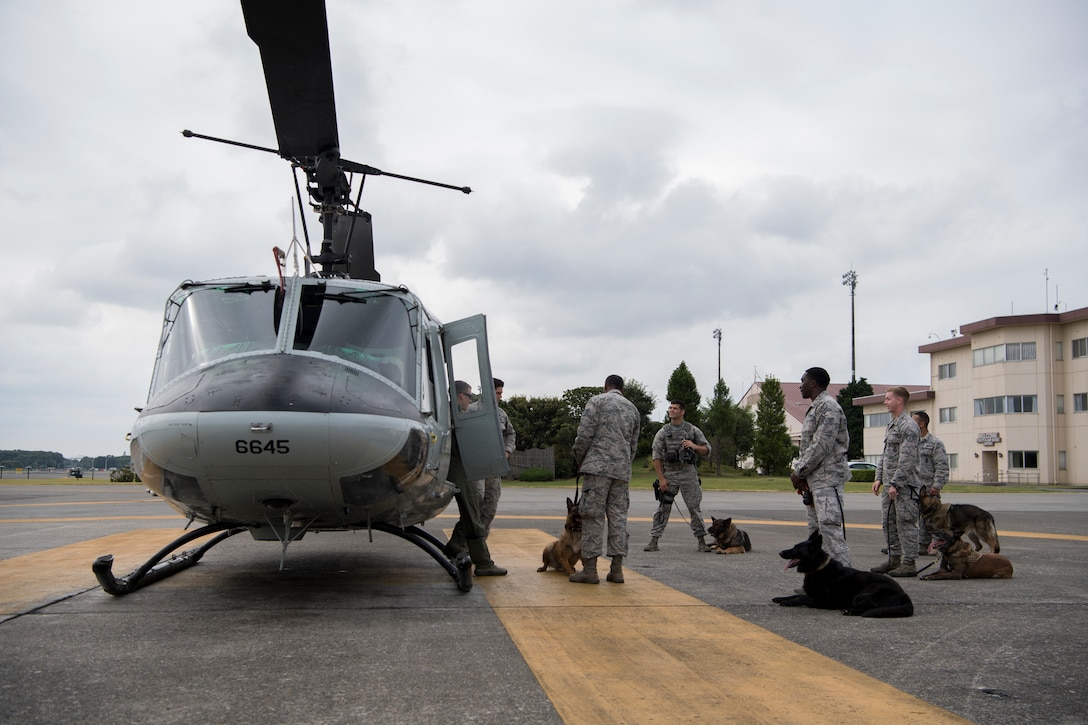 Members of the 374th Security Forces Squadron military working dog section listen to a safety briefing from Tech. Sgt. Dustin Sheffield, 459th Airlift Squadron UH-1N special mission aviator, prior to MWD familiarization flight July 26, 2018, at Yokota Air Base, Japan.