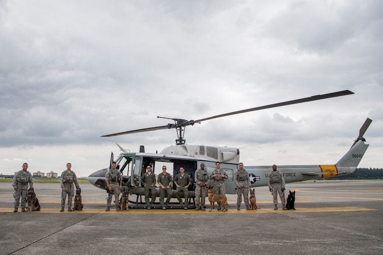 Members of the 374th Security Forces Squadron military working dog section, and the 458th Airlift Squadron UH-1N crew, pose for a photo July 26, 2018, at Yokota Air Base, Japan.