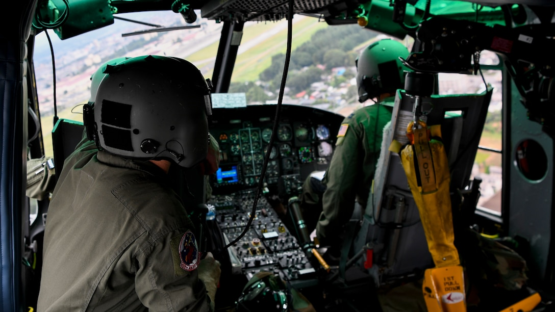 Members of the 459th Airlift Squadron fly a UH-1N helicopter during a 456 AS MWD familiarization flight July 26, 2018, over Yokota Air Base, Japan.