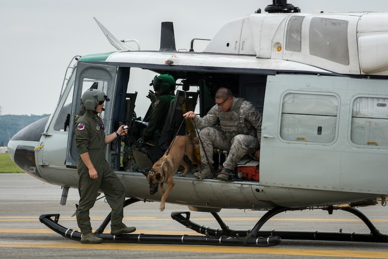 Staff Sgt. Michael Dacoron, 374th Security Forces Squadron military working dog handler, and Diesel, 374 SFS MWD, jump out of a UH-1N helicopter after a 459th Airlift Squadron MWD familiarization flight July 26, 2018, at Yokota Air Base, Japan.
