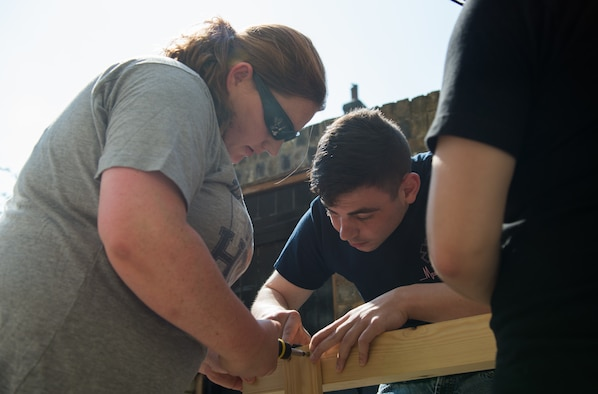 An Airman assigned to the 492nd Fighter Squadron, assists Tech. Sgt. Sheila Titus, a manpower analyst assigned to the 48th Force Support Squadron, assemble a piece of framework at a local homeless shelter in Cambridge, England, July 21, 2018. Titus and volunteers across the Liberty Wing assist with painting, moving furniture and beautification projects that help improve the quality of life for shelter residents. (U.S. Air Force photo/Airman 1st Class Shanice Williams-Jones)