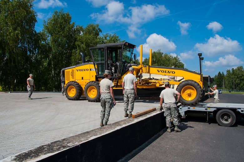 U.S. Air National Guard Airmen guide a Volvo 6710B Grader vehicle onto an off-loading dock during the Deployable Air Base System proof of concept exercise at the 31st Tactical Air Base, Poznan-Krzesiny, Poland, July 30, 2018. The exercise tests and enhances the ability to rapidly deploy within theatre, preposition equipment and enables the execution of current operations, exercises and contingencies. (U.S. Army photo by Spc. Craig Jensen)