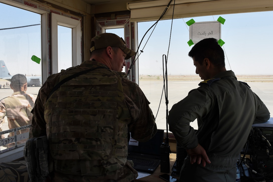 Senior Airman Timothy Feik, a 447th Air Expeditionary Group air traffic controller, advises an Iraqi Air Force controller July 19, 2018, at Qayyarah Airfield West, Iraq. The air traffic controllers at Q-West are a-part of the train, advise and assist mission with the Iraqi Air Force. (U.S. Air Force photo by Tech. Sgt. Caleb Pierce)