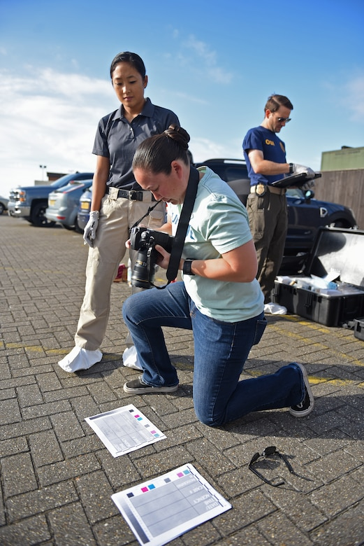 U.S. Air Force Senior Airman Alexandra West, 100th Air Refueling Wing Public Affairs broadcast journalist, documents a photo identifier before going into a simulated crime scene during crime scene processing training at RAF Mildenhall, England, Aug. 1, 2018. The training included members of Air Force Office of Special Investigations Detachment 512, 100th Security Forces Squadron Intelligence and Investigations unit and 100th ARW Public Affairs, who worked together to compare and develop crime scene processing skills. (U.S. Air Force photo by Senior Airman Luke Milano)