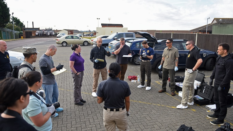U.S. Air Force Special Agent Mark Stuetzel, Air Force Office of Special Investigations Detachment 512, briefs Airmen during crime scene investigation processing training session at RAF Mildenhall, England, Aug. 1, 2018. This was the first time the three agencies came together to conduct crime scene investigation training at RAF Mildenhall. (U.S. Air Force photo by Senior Airman Luke Milano)