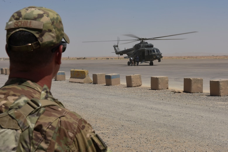 Senior Master Sgt. Adam Schill, 447th Air Expeditionary Group Detachment 1 superintendent, watches people board an Iraqi Air Force helicopter July 19, 2018, at Qayyarah Airfield West, Iraq. The air traffic controllers assigned to the 447th AEG, assist Iraqi Air Force controllers with various types of aircraft movement at the airfield. (U.S. Air Force photo by Tech. Sgt. Caleb Pierce)
