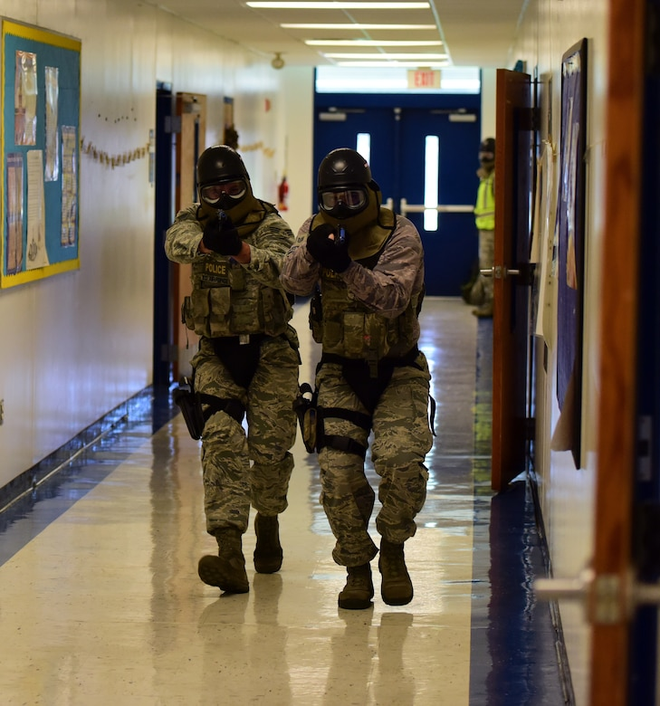 U.S. Air Force Defenders from the 325th Security Forces Squadron move toward the sound of simulated gunfire during an active -shooter training exercise at Tyndall Elementary School outside of Tyndall Air Force Base, Florida, July 30, 2018. The exercise allowed Tyndall defenders the opportunity to train in simulated real-world scenarios in a new setting, aiding them in their execution of force protection programs. The squadron oversees personnel, information, and industrial security procedures for more than 6,700 assigned personnel. (U.S. Air Force photo by Senior Airman Isaiah J. Soliz)