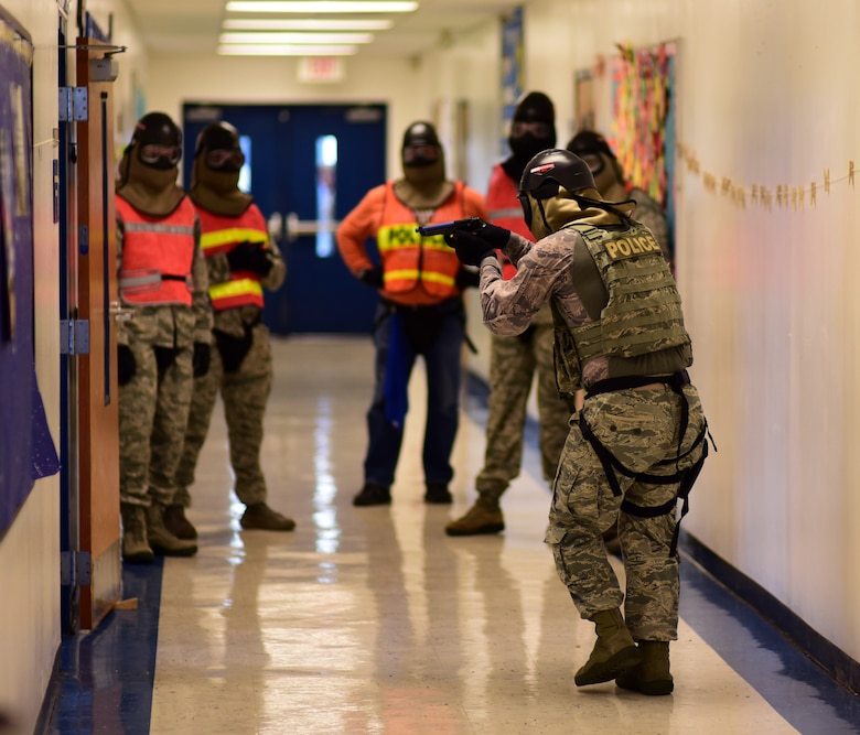 U.S. Air Force senior leadership and exercise evaluators observe as Tech. Sgt. Eric Lawrence, 325th Security Forces Squadron flight chief, tactically approaches a doorway during an active -shooter training exercise at Tyndall Elementary School outside of Tyndall Air Force Base, Florida, July 31, 2018. The exercise allowed Team Tyndall defenders to approach simulated real-world scenarios in a new environment. Tyndall defenders perform a plethora of duties to include: law enforcement, installation security, pass and registration, military working dog, anti -terrorism, resource protection and installation security services. (U.S. Air Force photo by Senior Airman Isaiah J. Soliz)
