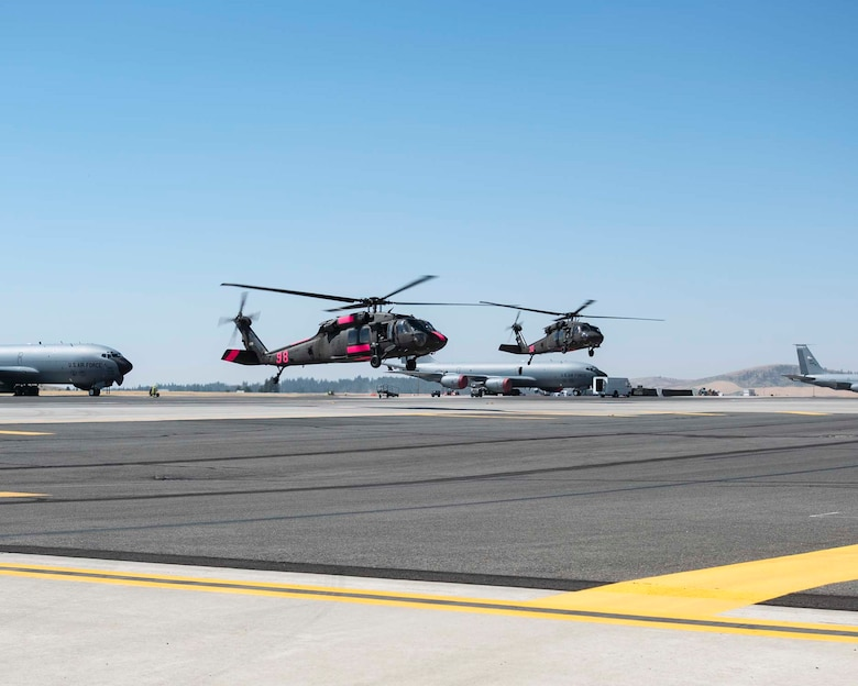 Two Black Hawk helicopters from Joint-Base Lewis-McChord land at Fairchild Air Force Base, Wash. in support of firefighting efforts in eastern Washington August 1, 2018. The helicopters will primarily be used as water buckets and can carry nearly 660 gallons of water at one time. (U.S. Air National Guard photo by Tech. Sgt. Michael Brown)