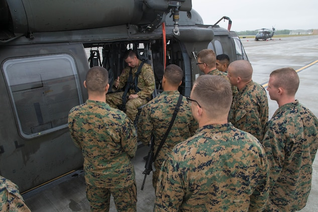 Squad Leaders and select support staff, from the 4th Marine Division Annual Rifle Squad competition, receive lessons on how to properly board and ride in a U.S. Army Sikorsky UH-60 Black Hawk at Joint Base Elmendorf-Richardson, Anchorage, Alaska, August 1, 2018. Squad leaders from the Annual Rifle Squad Competition were air-lifted throughout the training sites in order to conduct route reconnaissance before the commencement of the four day competition. (U.S. Marine Corps photo by Lance Cpl. Samantha Schwoch/released)