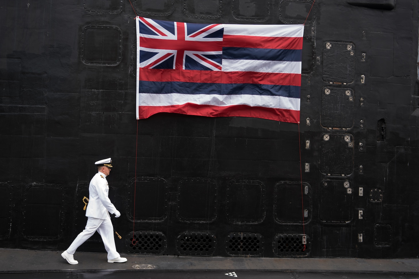 Capt. Richard Seif, commander, Submarine Squadron One, walks to the podium on the Virginia-class fast-attack submarine USS Hawaii (SSN 776) during a change of command ceremony on the submarine piers in Joint Base Pearl Harbor-Hickam, August 2. Cmdr. Sterling S. Jordan relieved Cmdr. John C. Roussakies as Hawaii's commanding officer.