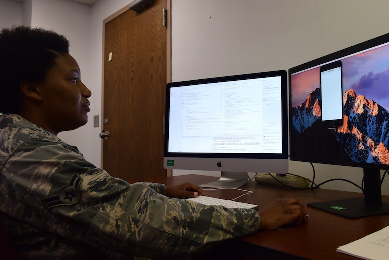 Airman 1st Class Ebony Crawford, 595th Strategic Communication Squadron strategic software programmer, who led the iPhone programming section for the 2018 Air and Space Show app, reviews the code for the program June 6, 2018, at Offutt Air Force Base, Nebraska. This year's app will involve live updates on parking and performers. (U.S. Air Force photo by Staff Sgt. Rachel Hammes)