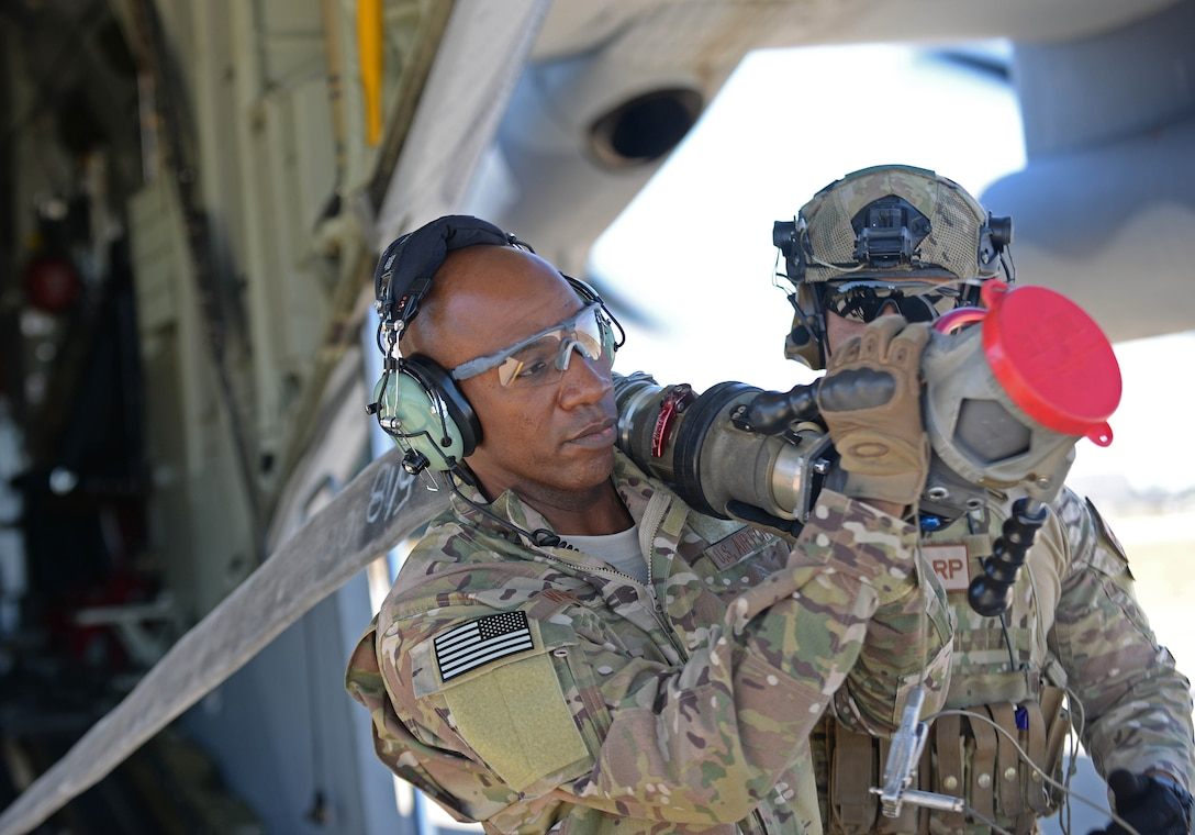 Chief Master Sgt. of the Air Force Kaleth O. Wright carries a fuel hose from a MC-130J II Commando during a Forward Area Refueling Point exercise at RAF Mildenhall, England, Aug. 2, 2018. During the visit, Wright met with Airmen from multiple units to ask about their needs and see how they accomplish the mission. (U.S. Air Force photo by Senior Airman Luke Milano)