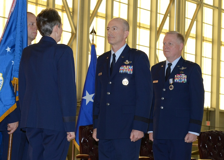 Brig. Gen. Christopher P. Azzano (center), accepts command of the Air Force Test Center from Gen. Ellen Pawlikowski, Air Force Materiel Command commander, during a change-of-command ceremony Aug. 3 at Edwards Air Force Base. Azzano replaces Maj. Gen. David Harris (right) who is retiring from the Air Force. (U.S. Air Force photo by Kenji Thuloweit)