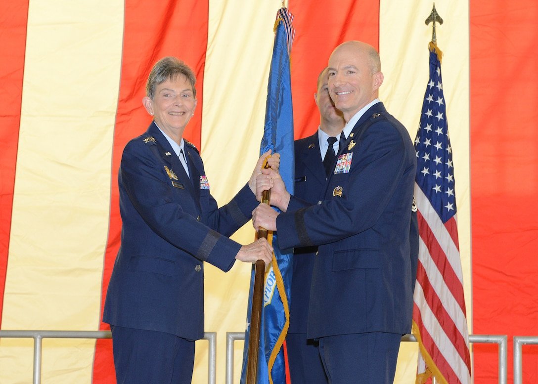 Brig. Gen. Christopher P. Azzano poses with the Air Force Test Center guidon with the commander of Air Force Materiel Command, Gen. Ellen Pawlikowski, during a change-of-command held in Hangar 1600 at Edwards Air Force Base, Aug. 3. (U.S. Air Force photo by Kenji Thuloweit)