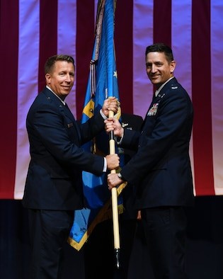 Two men hold a flag.