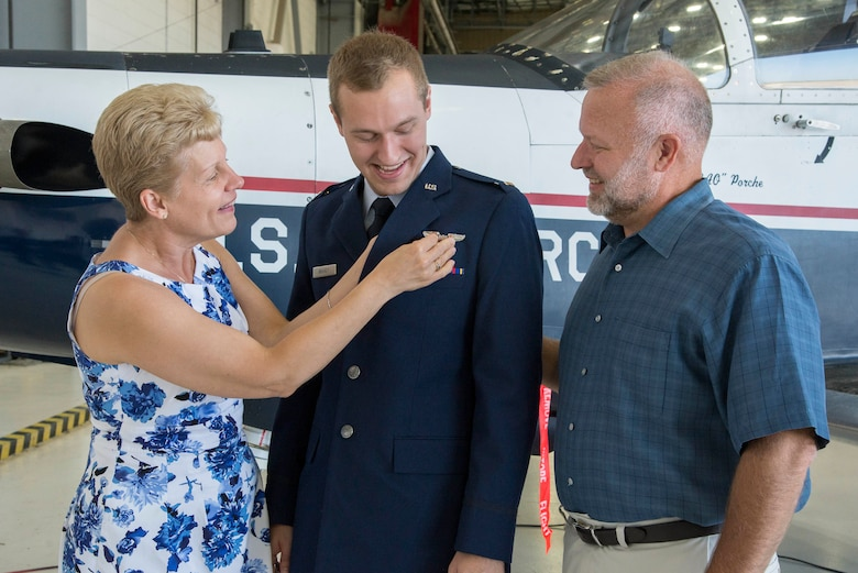 The parents of 2nd Lt. Nickolas Brandt, Pilot Training Next student, pin on his aeronautical wings during his graduation August 3, 2018, at the Armed Forces Reserve Center, Austin, Texas. PTN is a program to explore and potentially prototype a training environment that integrates various technologies to produce pilots in an accelerated, cost efficient, learning-focused manner.  (U.S. Air Force photo by Sean M. Worrell)