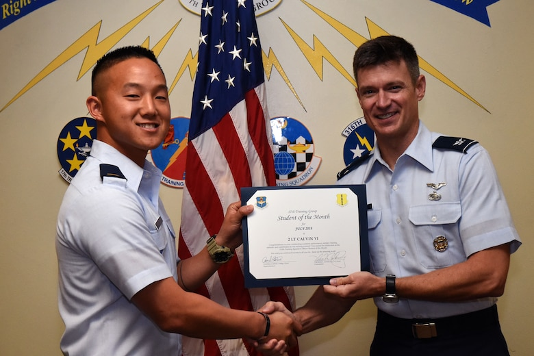 U.S. Air Force 2nd Lt. Calvin Yi, 315th Training Squadron student, receives the 315th Training Squadron Officer Student of the Month award from Col. Thomas Coakley, 17th Training Group commander, at Brandenburg Hall on Goodfellow Air Force Base, Texas, Aug. 3, 2018. The 315th TRS vision is to develop combat-ready intelligence, surveillance and reconnaissance professionals and promote an innovative squadron culture and identity unmatched across the U.S. Air Force. (U.S. Air Force photo by Airman 1st Class Seraiah Hines/Released)