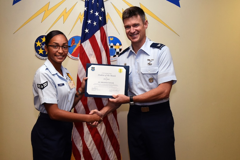 U.S. Air Force Airman 1st Class Brianna Taylor, 315th Training Squadron student, receives the 315th Training Squadron Student of the Month award from Col. Thomas Coakley, 17th Training Group commander, at Brandenburg Hall on Goodfellow Air Force Base, Texas, Aug. 3, 2018. The 315th TRS vision is to develop combat-ready intelligence, surveillance and reconnaissance professionals and promote an innovative squadron culture and identity unmatched across the U.S. Air Force. (U.S. Air Force photo by Airman 1st Class Seraiah Hines/Released)