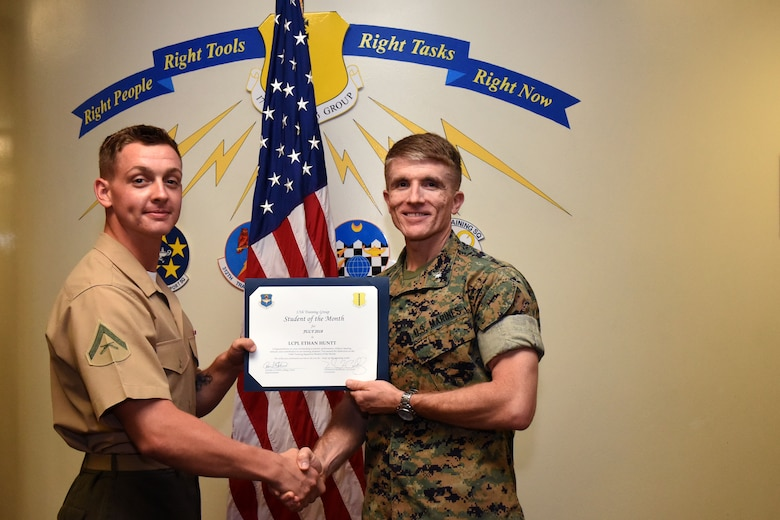 The 17th Training Group Student of the Month spotlight for July 2018, U.S. Marine Corp Lance Cpl. Ethan Huntt, 316th Training Squadron student, holds his award with Lt. Col. Earl Patterson, Marine Corps Detachment at Goodfellow commander, at Brandenburg Hall on Goodfellow Air Force Base, Texas, Aug. 3, 2018. Huntt is the Goodfellow Student of the Month spotlight for July 2018, a series highlighting Goodfellow students. (U.S. Air Force photo by Airman 1st Class Seraiah Hines/Released)