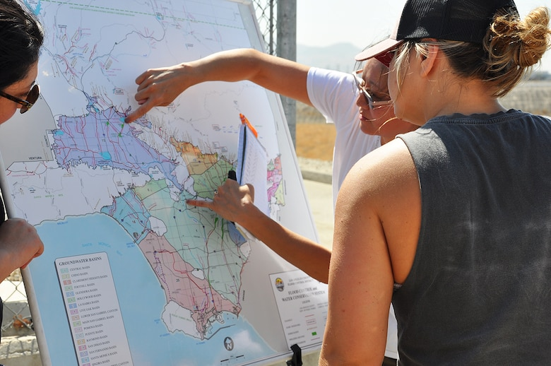 Eileen Takata, lead water resources planner, U.S. Army Corps of Engineers Los Angeles District, second from right, shows the area of responsibility for the Corps and the Los Angeles County Flood Control District in managing flood risk in the Greater Los Angeles Basin area during a July 25 visit to see water storage areas near Hansen Dam.